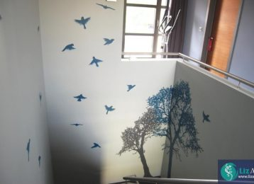 Muurschildering van decoratieve bomen met vogels in de traphal