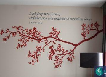 Muurschildering tak met een citaat in een hotelkamer