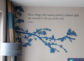 Decoratieve muurschildering tak met een citaat in een hotelkamer