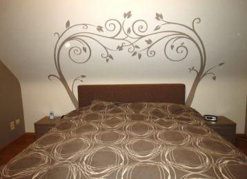 Muurschildering van elegante klimplanten boven het bed