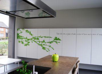 Decoratieve wandschildering tak met slogan op de keukenkast