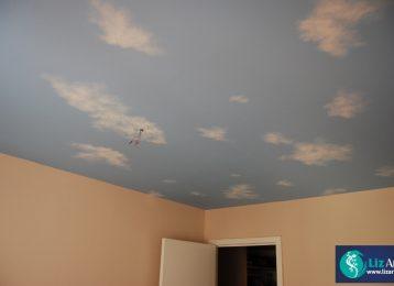 Plafondschildering van een blauwe lucht met wolkjes
