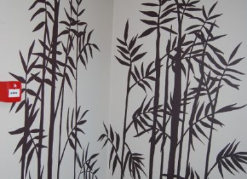 Decoratieve muurschildering van bamboe met een citaat