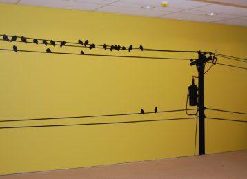 Muurschildering van vogels en elektriciteitsmast