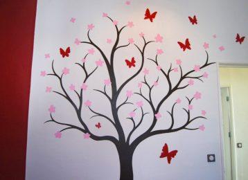 Decoratieve muurschildering boom in bloei met fladderende vlinders