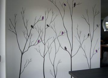 Decoratieve muurschildering met dunne boompjes met vogels er in.