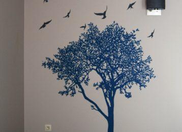 Muurschildering van een blauwe boom met vogels er rond