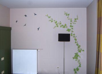 Muurschildering klimop in een hotelkamer