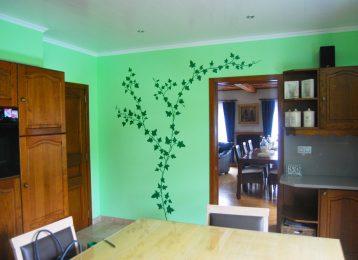 Decoratieve wandschildering van klimop op lichtgroene muur in de keuken