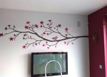 Muurschildering koolmees op bloesemtak in de woonkamer