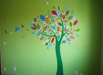 Decoratieve groene wandschildering boom met kleurrijke bladeren en vogels