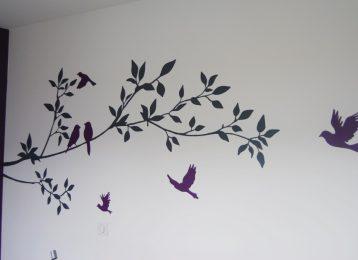 Decoratieve schildering silhouetten van paarse vogels op tak