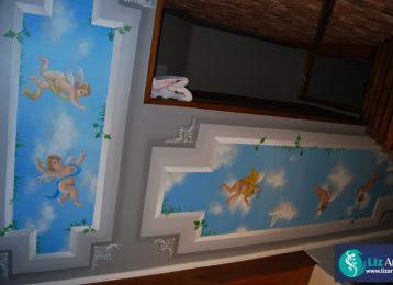 Muurschildering met engeltjes op het plafond boven een trap