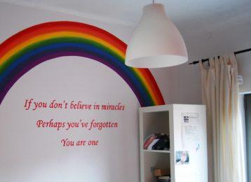 Muurschildering regenboog met spreuk