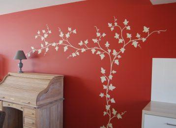 Decoratieve wandschildering van witte klimop op rode muur in de woonkamer