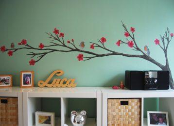Muurschildering van een tak met roodborstjes er op