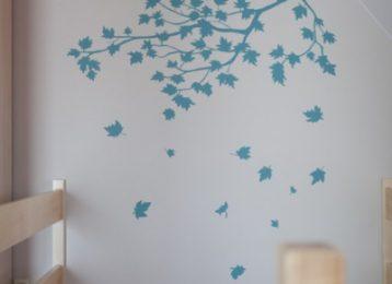 Muurschildering van een tak met vallende bladeren in een hotel