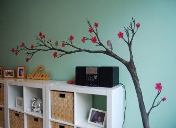 Muurschildering van een tak met bloemen en roodborstjes