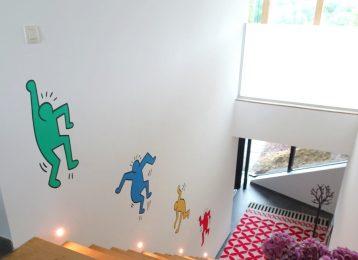 Decoratieve muurschildering bij trap in Keith Haring stijl