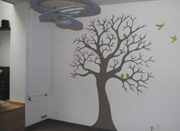 Decoratieve muurschildering van een winterboom met vogels